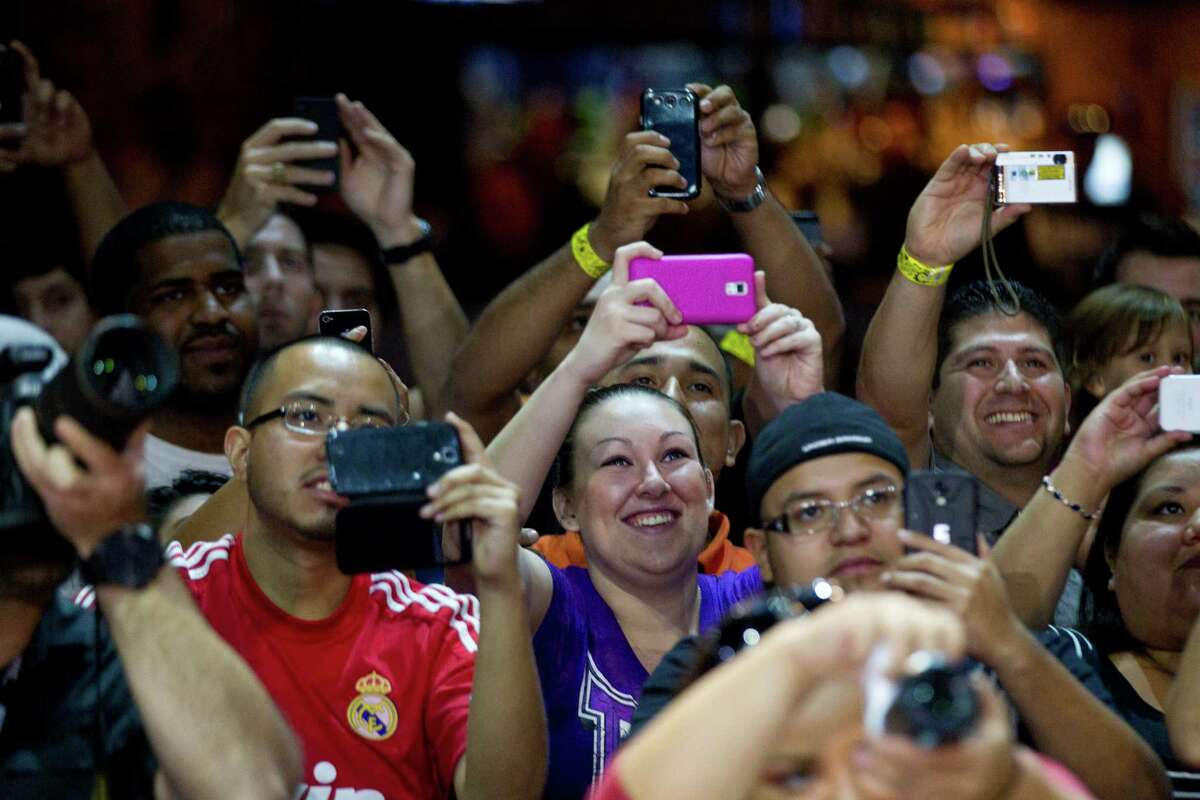 Fans take photos during an open workout for UFC 166 at the House of Blues Wednesday, Oct. 16, 2013, in Houston. The fights are scheduled for Saturday night at Toyota Center.