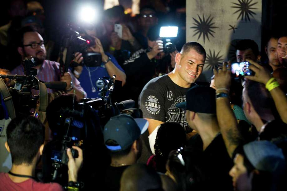 UFC heavyweight champion Cain Velasquez is surrounded by fans as he signs autographs following an open workout for UFC 166 at the House of Blues Wednesday, Oct. 16, 2013, in Houston. The fights are scheduled for Saturday night at Toyota Center. Photo: Brett Coomer, Houston Chronicle / © 2013 Houston Chronicle
