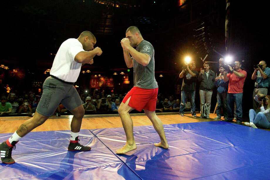 Daniel Cormier, left, works out with UFC heavyweight champion Cain Velasquez during an open workout for UFC 166 at the House of Blues Wednesday, Oct. 16, 2013, in Houston. The fights are scheduled for Saturday night at Toyota Center. Photo: Brett Coomer, Houston Chronicle / © 2013 Houston Chronicle