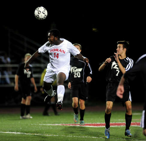 Foran's Cedrick Lingane heads the ball, during boys high school soccer action against Jonathan Law in Milford, Conn. on Wednesday October 16 2013. Photo: Christian Abraham / Connecticut Post
