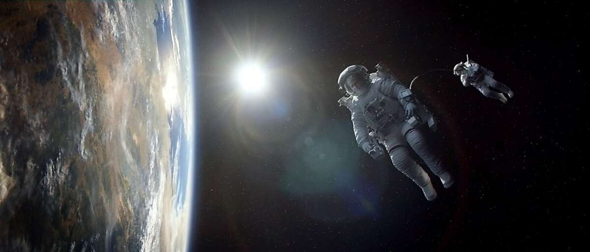 """Caption: (L-r) GEORGE CLOONEY as Matt Kowalski and SANDRA BULLOCK as Ryan Stone in Warner Bros. Pictures' dramatic thriller """"GRAVITY,"""" a Warner Bros. Pictures release."""