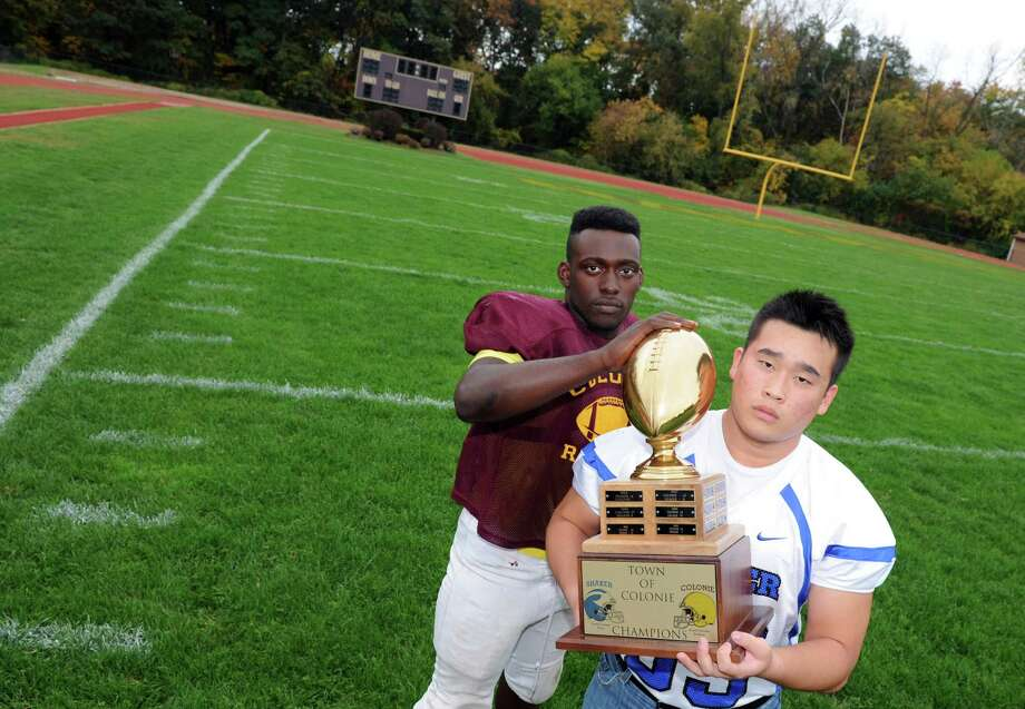 Colonie running back Kevon Johnson, left, and Shaker offensive guard Phil Chun with the Colonie Town Cup on Wednesday Oct. 16, 2013 in Colonie, N.Y. (Michael P. Farrell/Times Union) Photo: Michael P. Farrell / 00024286A