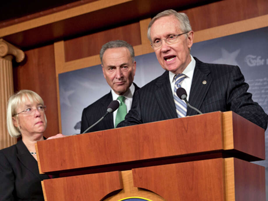 Senate Majority Leader Harry Reid, D-Nev., speaks with reporters after voting on a measure to avert a threatened Treasury default and reopen the government after a partial, 16-day shutdown, at the Capitol in Washington, Wednesday, Oct. 16, 2013, as Sen. Patty Murray, D-Wash., chair of the Senate Budget Committee, Sen. Chuck Schumer, D-N.Y., listen. Photo: J. Scott Applewhite, AP / AP