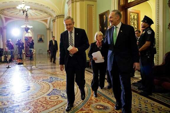 Senate Majority Leader Sen. Harry Reid, D-Nev., left, walks off the Senate floor with Sen. Chuck Schumer, D-N.Y., after the crucial vote Wednesday.