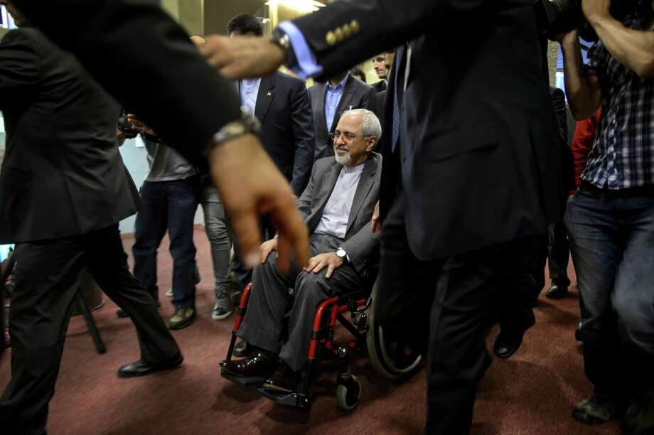 Iranian Foreign Minister Mohammad Javad Zarif leaves in his wheelchair a press conference closing two days of closed-door nuclear talks on October 16, 2013 in Geneva. World powers pored over what Iran billed as a breakthrough proposal to end the decade-long standoff over its nuclear programme, amid a growing diplomatic thaw but stark warnings from Israel.  AFP PHOTO / FABRICE COFFRINIFABRICE COFFRINI/AFP/Getty Images Photo: FABRICE COFFRINI / AFP
