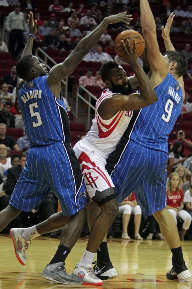 Orlando Magic shooting guard Victor Oladipo left, and the Magic's Nikola Vucevic right, double team  the Houston Rockets shooting guard James Harden center, during first quarter of NBA preseason game action at the Toyota Center Wednesday, Oct. 16, 2013, in Houston.  ( James Nielsen / Houston Chronicle ) Photo: James Nielsen, Houston Chronicle