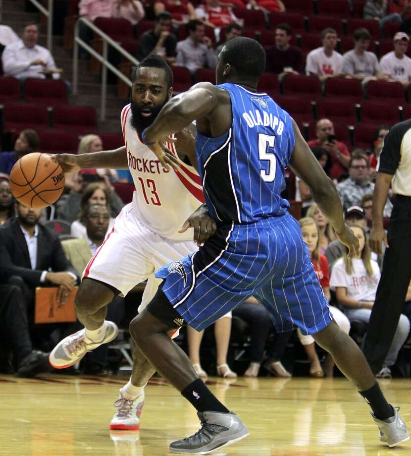Houston Rockets shooting guard James Harden drives the ball past Orlando Magic shooting guard Victor Oladipo right, during first quarter of NBA preseason game action at the Toyota Center Wednesday, Oct. 16, 2013, in Houston.  ( James Nielsen / Houston Chronicle ) Photo: James Nielsen, Houston Chronicle