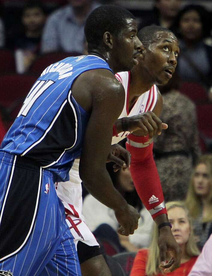 Orlando Magic power forward Andrew Nicholson left, Houston Rockets center Dwight Howard right, during the first quarter of NBA preseason game action at the Toyota Center Wednesday, Oct. 16, 2013, in Houston.  ( James Nielsen / Houston Chronicle ) Photo: James Nielsen, Houston Chronicle