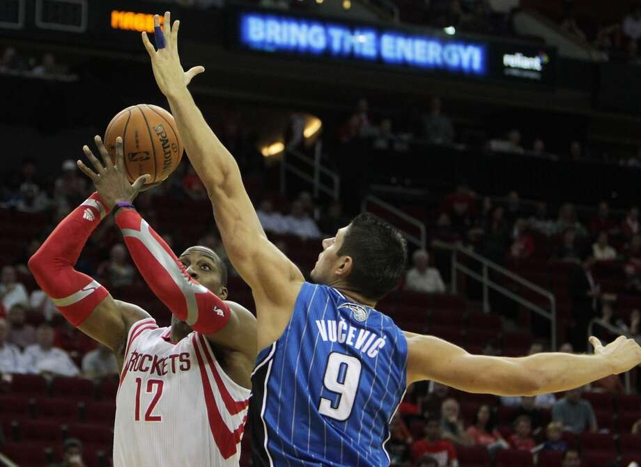 Houston Rockets center Dwight Howard left, shoots the ball over Orlando Magic center Nikola Vucevic right, during the first quarter of NBA preseason game action at the Toyota Center Wednesday, Oct. 16, 2013, in Houston.  ( James Nielsen / Houston Chronicle ) Photo: James Nielsen, Houston Chronicle