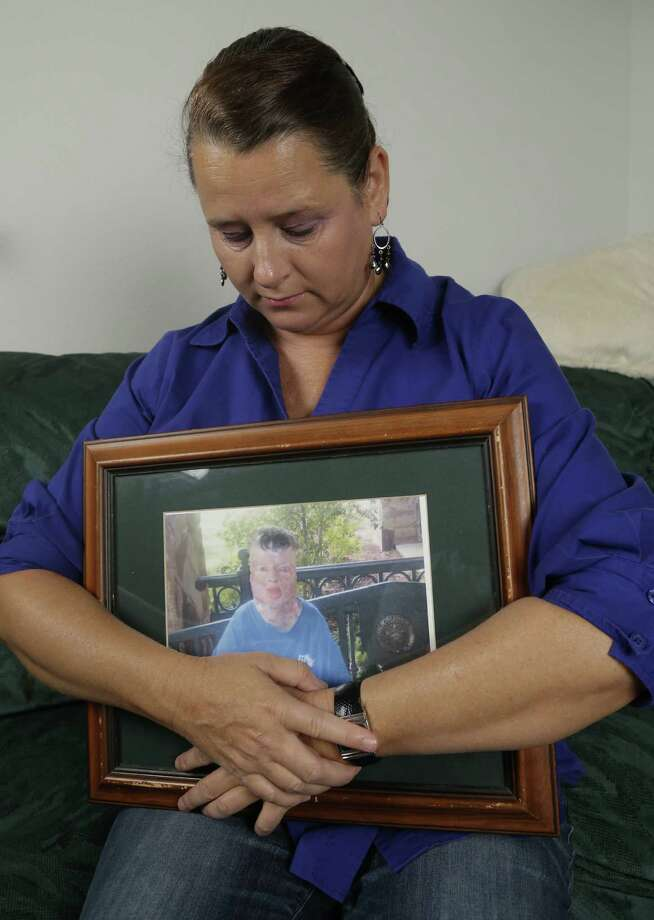 Colleen Middleton holds a photograph of her son after an interview last month in Galveston. The boy, Robert, lived for 13 years after he was severely burned on his 8th birthday. Photo: Associated Press