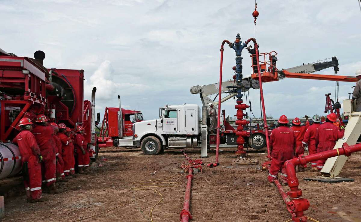 Workers watch as the frac tree is removed from a well at a ranch southwest of Ben Bolt, Texas, on Wednesday, Sept. 11, 2013. The well, located near the Jim Wells and Duvall County line, was drilled to a depth of over one mile.