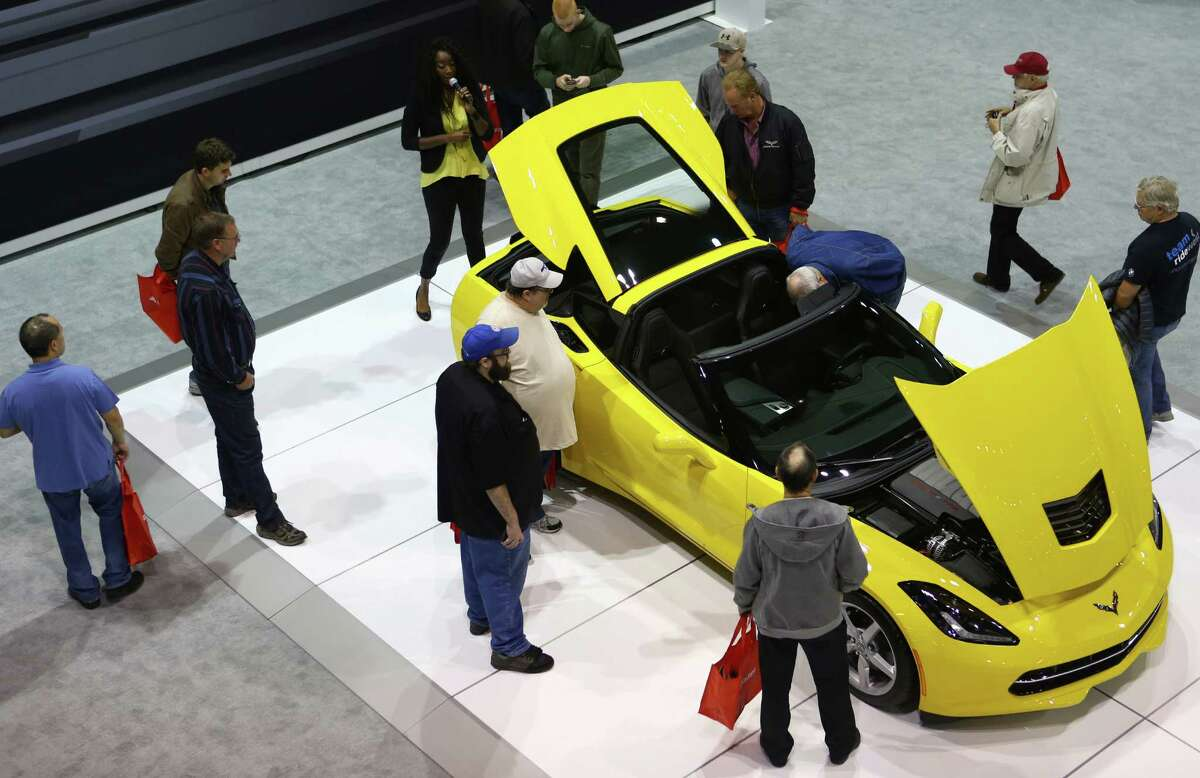 People gather around a Chevy Corvette Stingray during the opening day of the Seattle Auto Show. Click through the gallery to see some of the cars on display at the show.