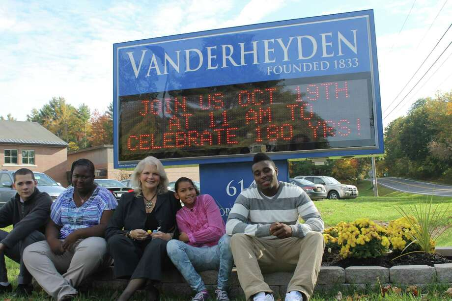 Vanderheyden president and CEO Karen Carpenter Palumbo, center, poses in front of the nonprofit's new sign on Cooper Hill Road in Wynantskill with students (from left) Ben, Natiya, Dorothy and Donell. (Jennifer Patterson/Times Union)