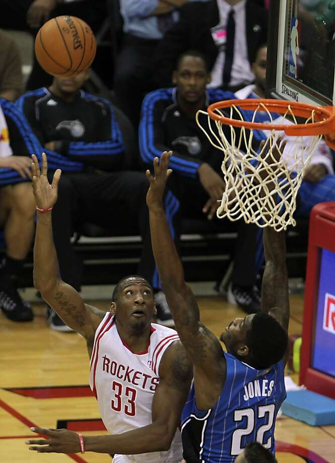 Houston Rockets small forward Robert Covington left, scores a basket over Orlando Magic power forward Solomon Jones right, during the fourth quarter of NBA preseason game action at the Toyota Center Wednesday, Oct. 16, 2013, in Houston.  ( James Nielsen / Houston Chronicle ) Photo: Houston Chronicle