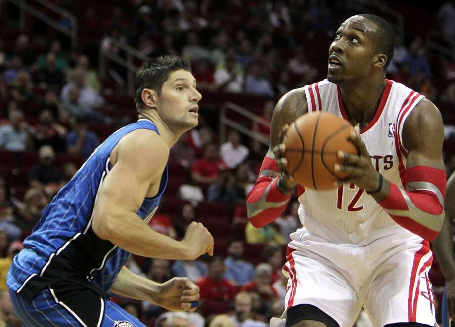 Houston Rockets center Dwight Howard right, eyes the basket as Orlando Magic center Nikola Vucevic right, looks on during the second quarter of NBA preseason game action at the Toyota Center Wednesday, Oct. 16, 2013, in Houston.  ( James Nielsen / Houston Chronicle ) Photo: Houston Chronicle