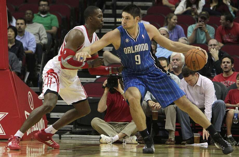 Houston Rockets center Dwight Howard left, and Orlando Magic center Nikola Vucevic right, during the second quarter of NBA preseason game action at the Toyota Center Wednesday, Oct. 16, 2013, in Houston.  ( James Nielsen / Houston Chronicle ) Photo: Houston Chronicle