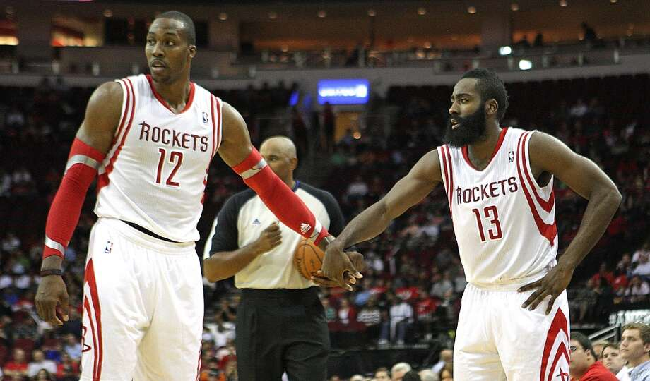 Houston Rockets center Dwight Howard left, slaps hands with Rockets shooting guard James Harden right, during the second quarter of NBA preseason game action at the Toyota Center Wednesday, Oct. 16, 2013, in Houston.  ( James Nielsen / Houston Chronicle ) Photo: Houston Chronicle