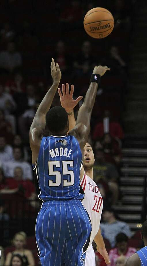 Orlando Magic shooting guard E'Twaun Moore left, shoots the ball over Houston Rockets power forward Donatas Motiejunas right, during the second quarter of NBA preseason game action at the Toyota Center Wednesday, Oct. 16, 2013, in Houston.  ( James Nielsen / Houston Chronicle ) Photo: Houston Chronicle