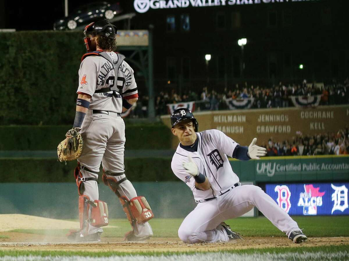 Jose Iglesias slides home with the Tigers' fourth run, scoring on a two-run double by Torii Hunter.