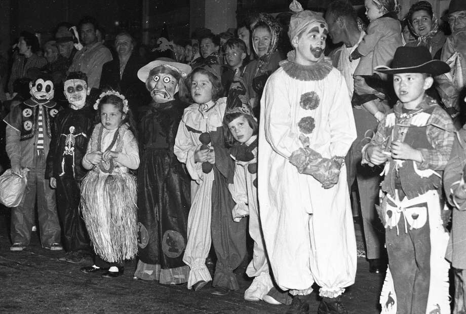 Oct. 31, 1948: Halloween in San Francisco. Note the large number of cowboys and clowns in these photos. Not sure  what the guy fourth from the left is, but he will be haunting my dreams. Photo: Chronicle Staff, The Chronicle