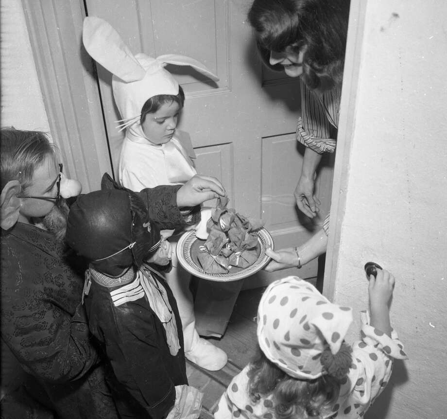 Oct. 31, 1953: Young San Franciscans trick or treat on Halloween. I'm guessing these were some kind of home made asbestos cookies on that tray. This was years before anyone worried about razor blades. Photo: Chronicle Staff, The Chronicle