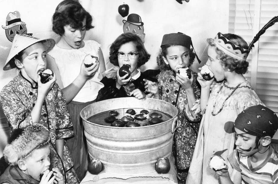 Oct. 27, 1955: Seven children bob for apples during a San Francisco party a few days before Halloween. In the center, seemingly without costumes, are the photographer's daughters Robin and Susan. Photo: Art Frisch, The Chronicle