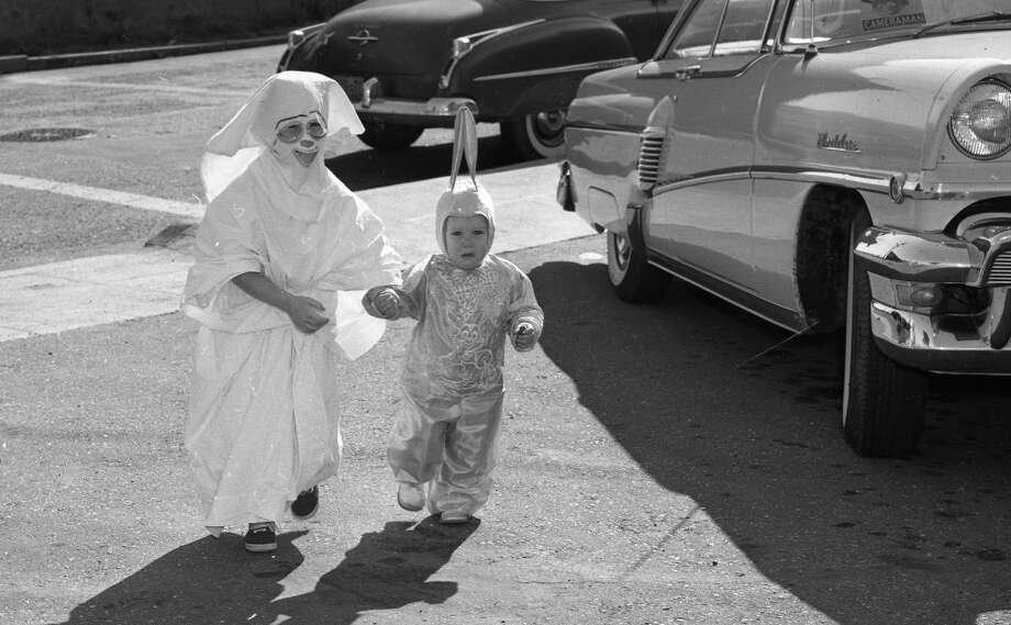 Oct. 31, 1957: Patricia and Susanne Gerber head to a party. That's a scary ghost, until you get to the tennis shoes. Note that San Franciscans parked on the sidewalks in 1957 as well. Photo: Art Frisch, The Chronicle