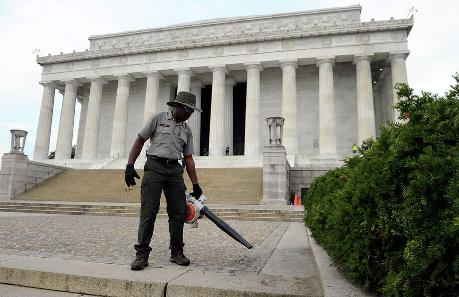 National Park Service employee Paul Fox of Washington, who had been off work for the last 16 days, uses a blower to clean the grounds of the Lincoln Memorial in Washington, Thursday, Oct. 17, 2013. Barriers went down at National Park Service sites and thousands of furloughed federal workers began returning to work throughout the country Thursday after 16 days off the job because of the partial government shutdown. Photo: Susan Walsh, AP / AP