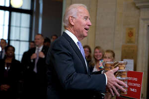 Vice President Joe Biden, left, greets Environmental Protection Agency workers with muffins as they return to work after 16 days of a government shutdown at the William Jefferson Clinton Federal Building in Washington on Thursday, Oct. 17, 2013.