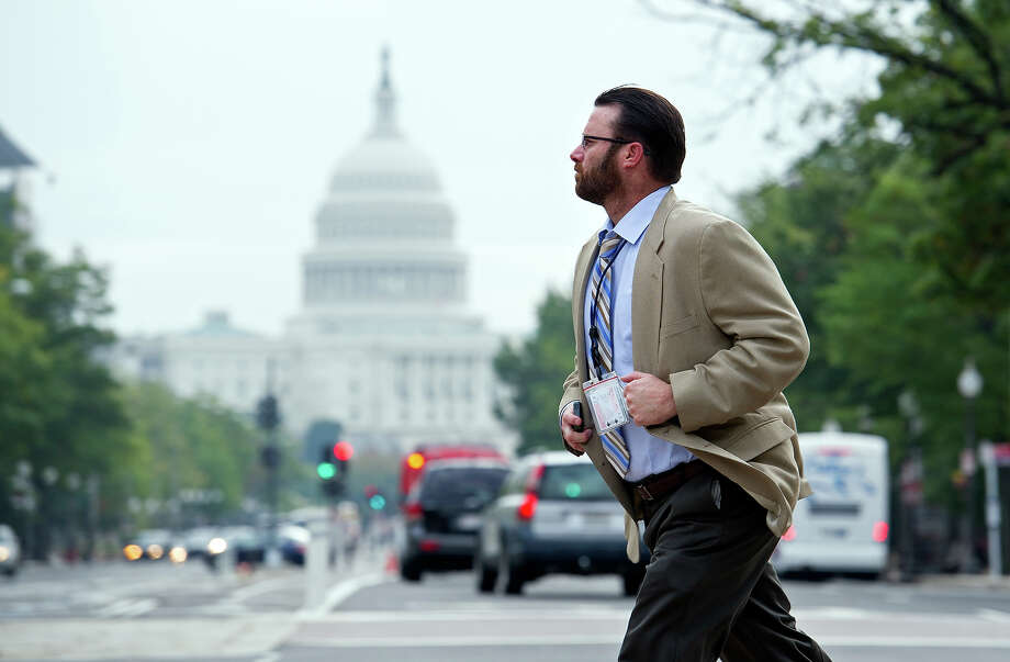 A man crosses Pennsylvania Ave., NW, in front of the Justice Department, in Washington, Thursday, Oct. 17, 2013. After 16 days of being off the job, thousands of furloughed federal workers are returning to work now that the government shutdown has been resolved. Photo: Cliff Owen, AP / FR170079 AP