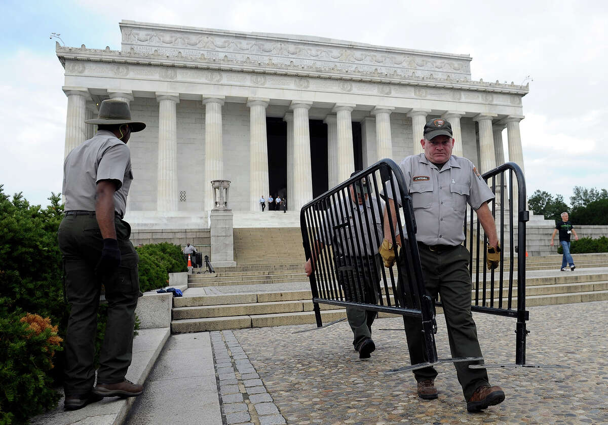 National Park Service employee James Mitchell, right, and others, remove barricades from the grounds of the Lincoln Memorial in Washington, Thursday, Oct. 17, 2013. Barriers went down at National Park Service sites and thousands of furloughed federal workers began returning to work throughout the country Thursday after 16 days off the job because of the partial government shutdown.