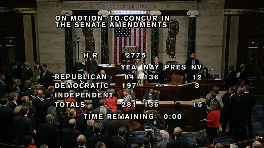 "In this image from House Television, with partial voting totals on the screen, a woman, at the rostrum just below the House presiding officer, seen between the ""yea"" and ""nay"" wording, is removed from the House chamber after she began shouting during the vote for the bill to end the partial 16-day government shutdown and to fund the government. The woman was described by lawmakers and aides as a long-time House stenographer. (AP Photo/House TV) Photo: Uncredited, ASSOCIATED PRESS / AP2013"