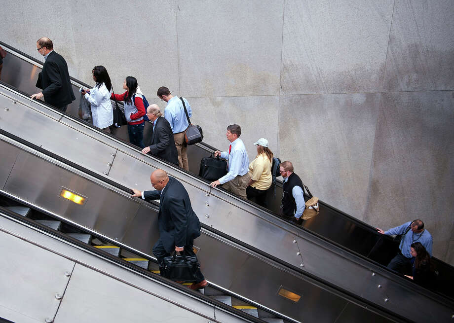 People exit a Metro subway station, by escalator, along Pennsylvania Ave., NW, in Washington, Thursday, Oct. 17, 2013. After 16 days of being off the job, thousands of furloughed federal workers are returning to work now that the government shutdown has been resolved. Photo: Cliff Owen, AP / FR170079 AP
