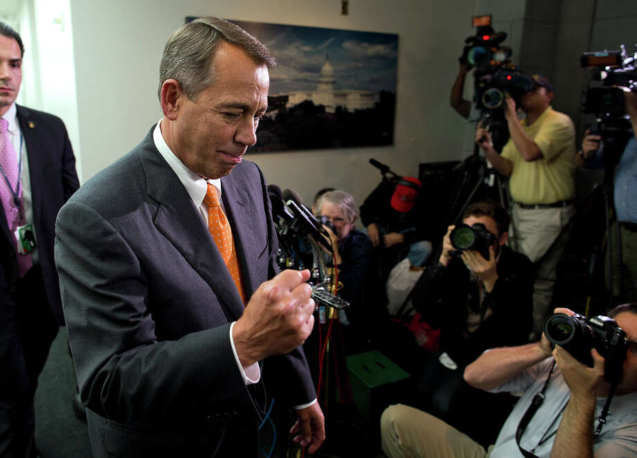 Speaker of the House Rep. John Boehner, R-Ohio, pumps his fist as he walks past reporters after a meeting with House Republicans on Capitol Hill on Wednesday, Oct. 16, 2013 in Washington. The partial government shutdown is in its third week and less than two days before the Treasury Department says it will be unable to borrow and will rely on a cash cushion to pay the country's bills. (AP Photo/ Evan Vucci) Photo: Evan Vucci, ASSOCIATED PRESS / AP2013