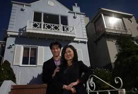 Shine Wu, left and Michelle Kim from Zephyr Real Estate stand in front of a home, Wednesday October 16, 2013, in San Francisco, Calif.