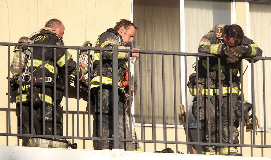 Firefighters recover after working a six-alarm fire at an apartment building Thursday morning in Redwood City. Four people were transported to the hospital with injuries, two of them minor, one moderate and one serious. Photo: Mathew Sumner, Associated Press