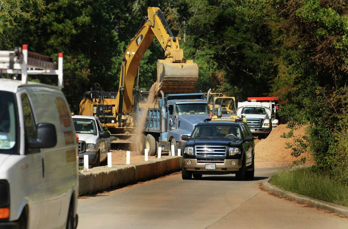 Traffic on Research Forest passes past workers instalingl the WiB segment pipeline at the corner of Crownridge and Research Forest. Construction on the new water pipeline running along Research Forest has traffic being diverted to one lane of traffic at different locations. Photo by David Hopper