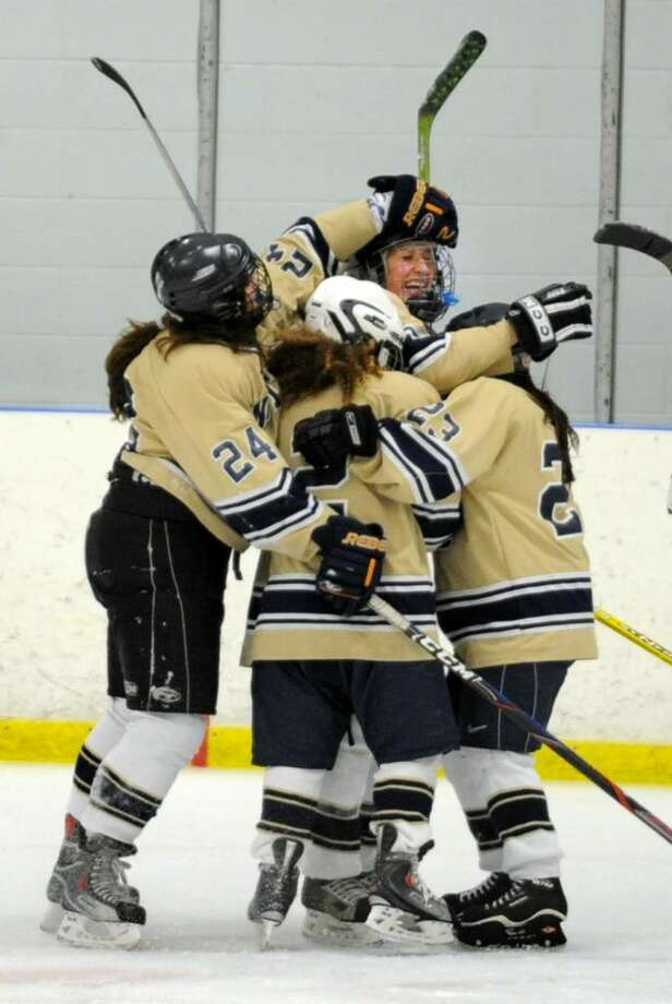 Notre Dame-Fairfield teammates gather around Olivia Stacey after her goal during the second period of Wednesday night's game against Guilford at the Milford Ice Pavilion. Photo: Autumn Driscoll / Connecticut Post