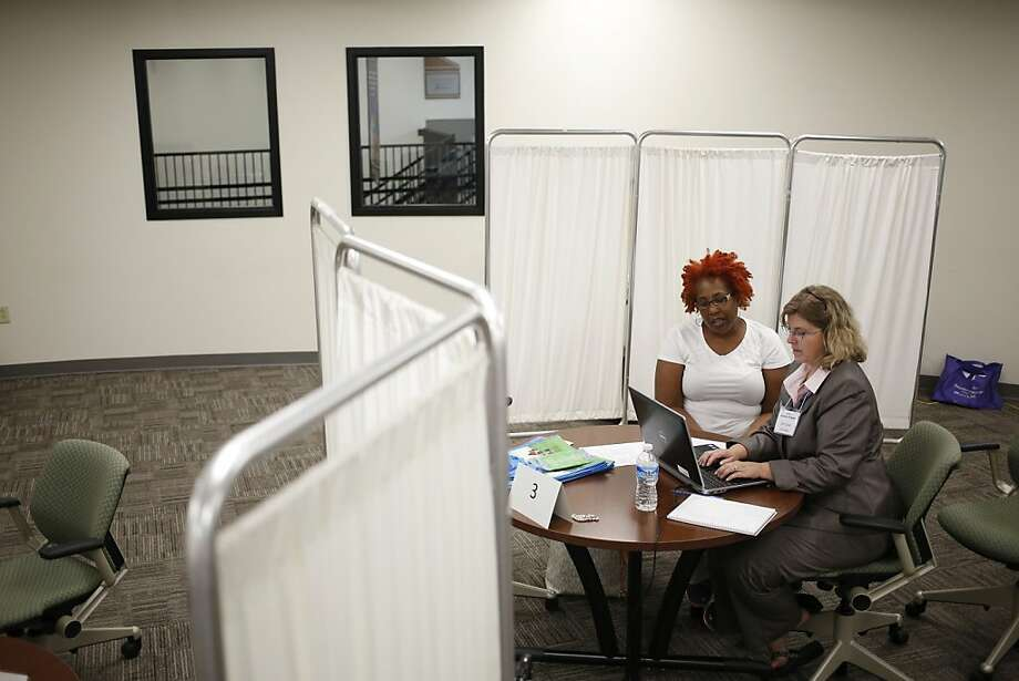 Christie Hartlage (right), of Kentucky Healthcare Connection helps an applicant in Louisville, Ky., research coverage options on the first day of Affordable Care Act enrollment. Photo: Luke Sharrett, New York Times
