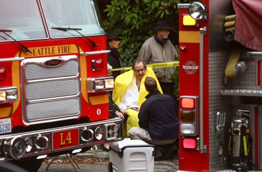 A Seattle firefighter speaks with a resident of a condo building that caught fire in Seattle's Capitol Hill neighborhood. (Joshua Trujillo, seattlepi.com)