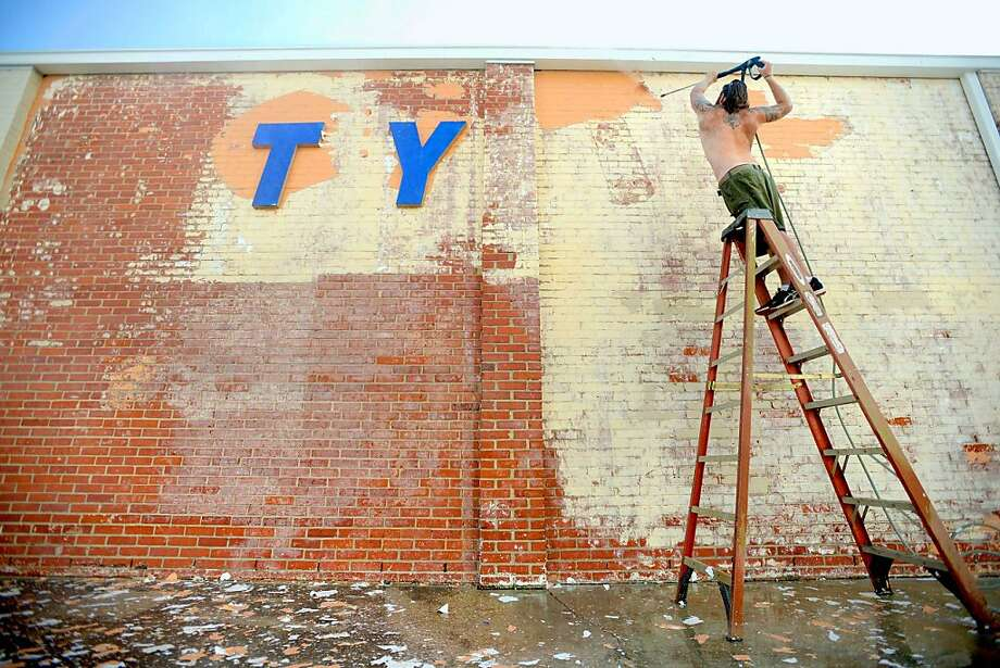 """Go figure:Tyler Stiles is supposed to be pressure-washing all the paint off a brick   wall at Carpet City in Fort Walton Beach, Fla., but for some reason he left the last two letters of """"City""""   untouched. Photo: Nick Tomecek, Associated Press"""