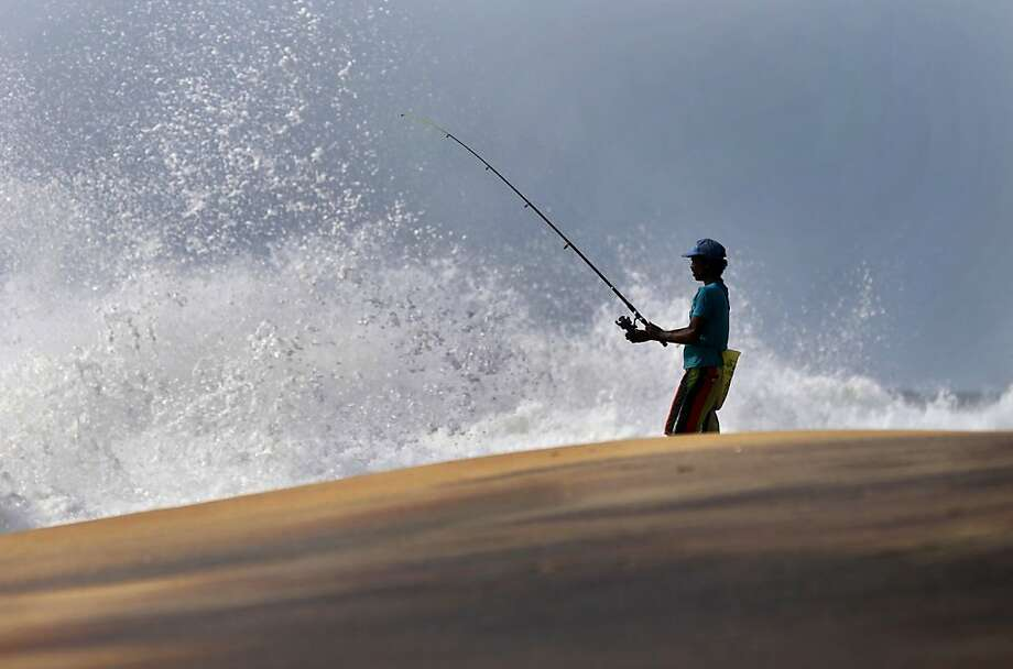 Despite rough surf, a Sri Lankan fisherman hopes to hook dinner in Colombo. Photo: Eranga Jayawardena, Associated Press
