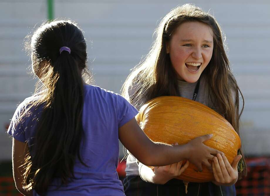 Happy Halloween hernia! Megan Clarke catches a pumpkin handed her by Jennessy Hernandez at Miami Shores Presbyterian Church in Miami Shores, Fla. Photo: Wilfredo Lee, Associated Press