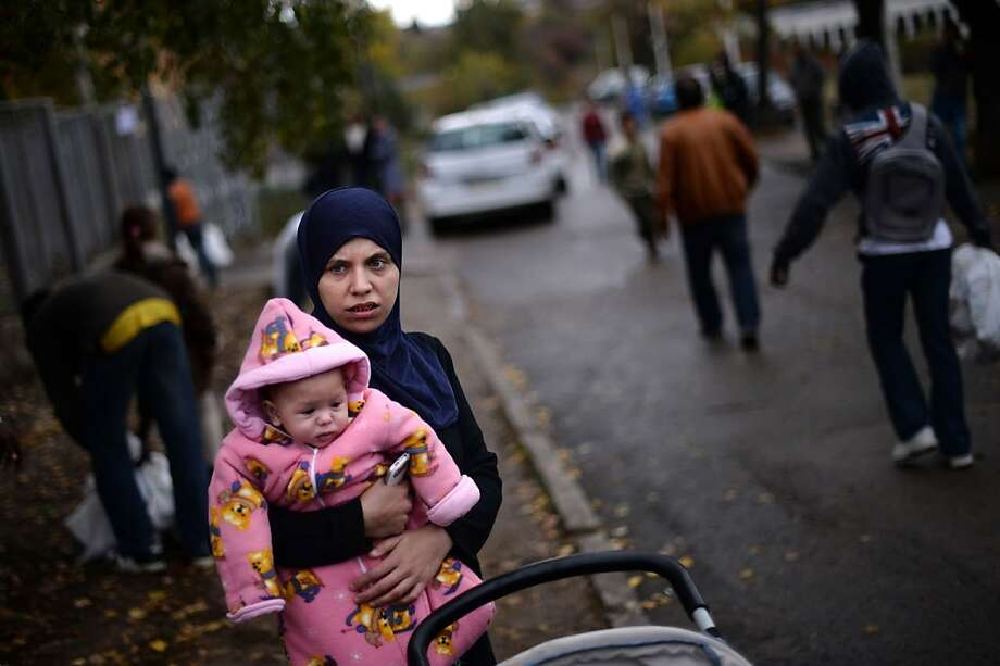 Bulgaria says no more:A refugee woman holds her baby as she waits to receive food distributed by Bulgaria's chief mufti to mark   the Muslim holiday of Eid al-Adha in Sofia. Bulgaria plans to build a fence on its southeastern   border with Turkey to prevent illegal Syrian immigrants from entering the country. Photo: Dimitar Dilkoff, AFP/Getty Images