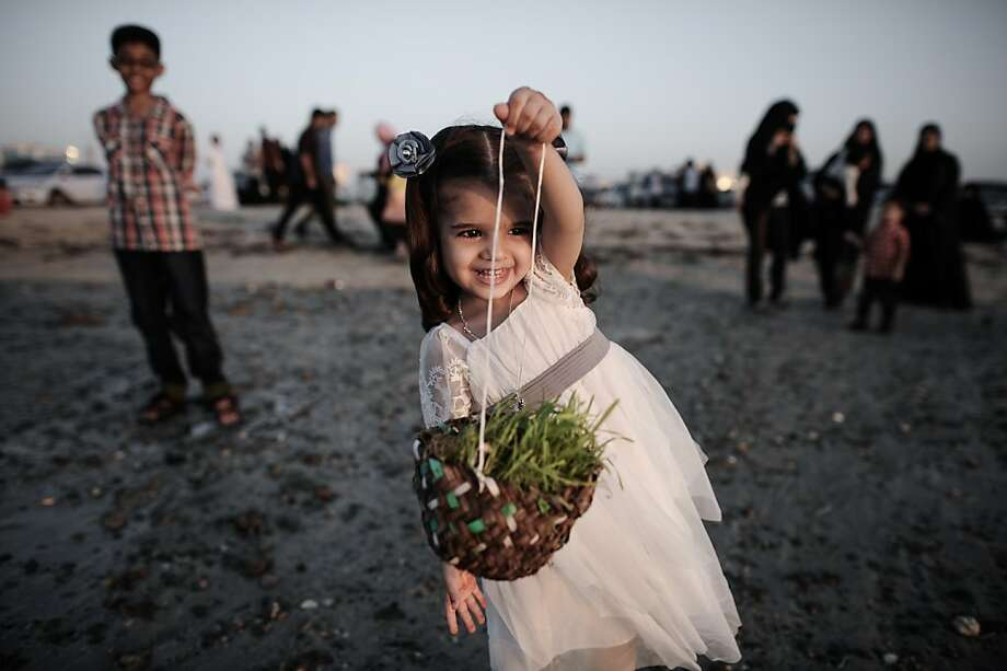 Bye ya, Haya Bya: A little girl swings a basket of Haya Bya plants in the Manama coastal suburb of Karbabad, Bahrain. The plants are traditionally thrown into the sea in some countries of the Gulf region during Eid al-Adha. Photo: Mohamed Al-Shaikh, AFP/Getty Images