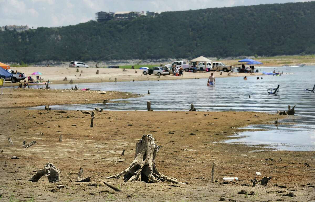 Stumps stick out of the ground, exposed by low water levels at Lake Travis in Austin.