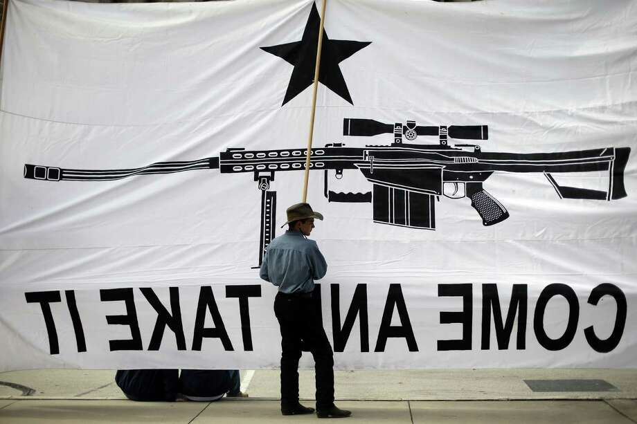"Austin Ehlinger helps hold a banner during a Guns Across America rally at the state Capitol in January. Some experts suggest that universal background checks could help keep guns out of the hands of certain ""dangerous people."" Photo: File Photo, Associated Press"