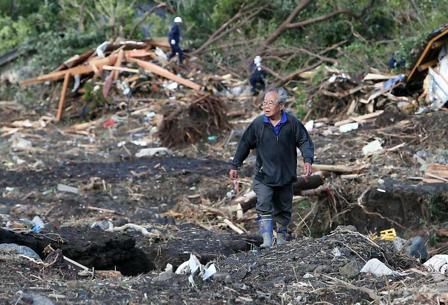 Death in typhoon's wake:Iwao Gomi searches for his brother and sister-in-law after a landslide buried 