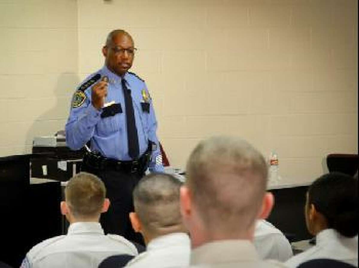 Chief McClelland shows cadets the Chief of Police Challenge Coin he has distributed to every classified and civilian employee. The department's core values are engraved in the coin.