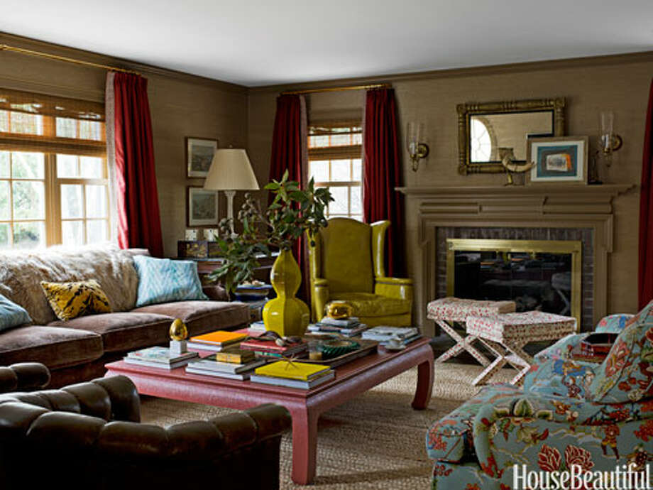 "Design Around the Fireplace Designer Meg Braff oriented the seating in this Colonial Revival house in Lattingtown, New York, around the fireplace. ""When there's a fireplace in a room, you want to be around it,"" Braff says. ""You can imagine a fire even if there isn't one."" A large-scale coffee table from Meg Braff Antiques & Decorations anchors the sofa and the chairs. A vintage chartreuse leather wing chair adds snap. Walls are covered in a taupe grass cloth from Hinson. Photo: JAMES MERRELL, HouseBeautiful.com / © James Merrell"